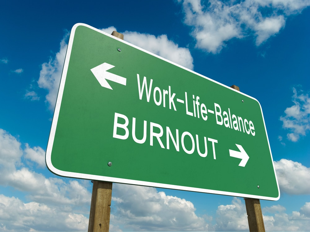 """Road sign photo with left arrow pointing to """"work-life-balance"""" and right arrow pointing to """"burnout"""""""